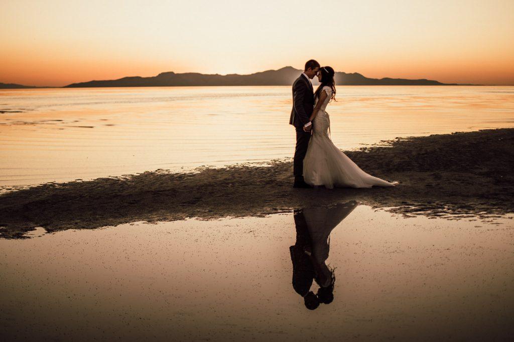 kiss at sunset great salt lake wedding mermaid wedding gown fitted with detailed belt sunset elopement #weddingphotographer #greatsaltlake #elopementwedding #love #married #mermaidweddinggown