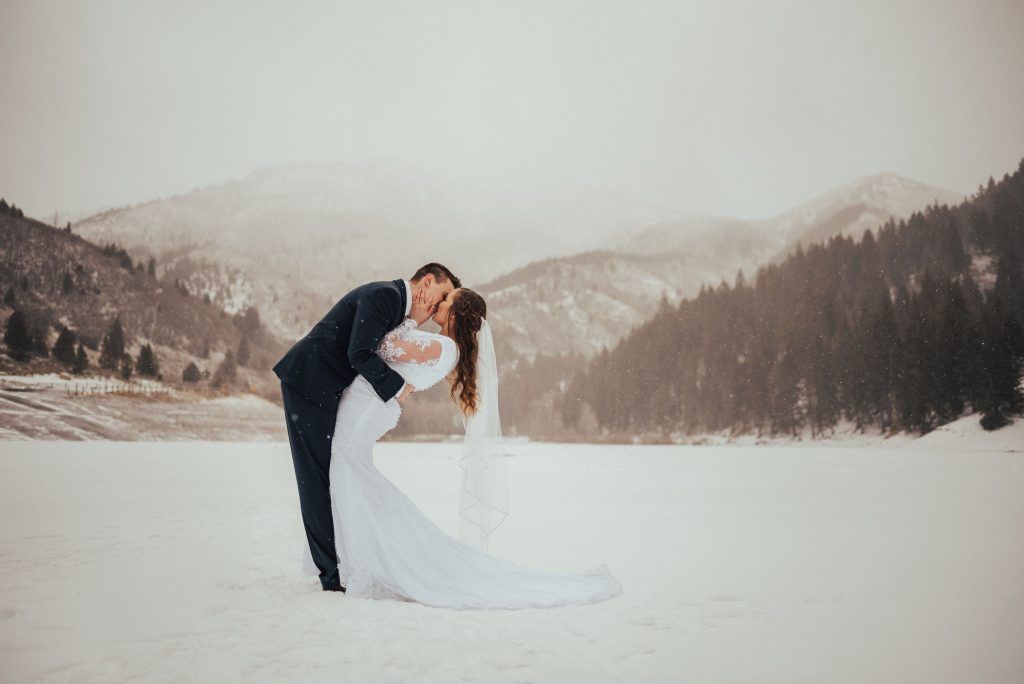 snowy wedding, mountain snow, snow elopement, kissing in the snow, bride with veil